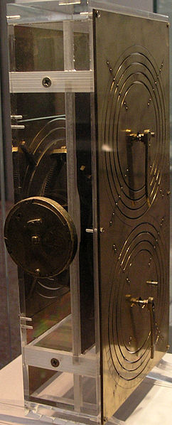 "Replica of the Antikythera Instrument: Based on the research of Professor Derek de Solla Price, in collaboration with the National Scientific Research Center ""Demokritos"" and physicist CH Karakalos who carried out the x-ray tomography of the original. This mechanism has been rebuilt to show the likely operation of the original. Price built a rectangular box of 33 cm X 17 cm X 10 cm with protective plates bearing Greek inscriptions of planets and operational information. Photo by Wikipedia user Marsyas (Creative Commons)"