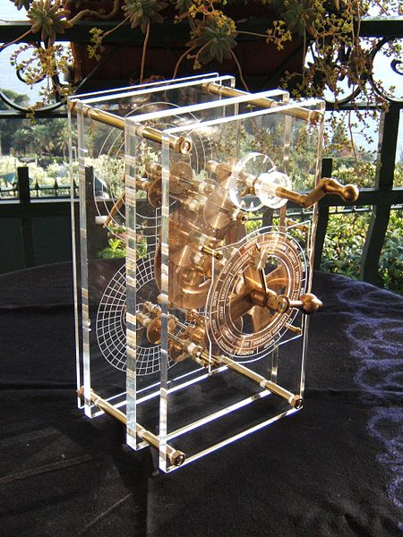 "A model of the Antikythera Mechanism. Based on the research of Professor Derek de Solla Price, in collaboration with the National Scientific Research Center ""Demokritos"" and physicist CH Karakalos who carried out the x-ray tomography of the original. This mechanism has been rebuilt to show the likely operation of the original. Price built a rectangular box of 33 cm X 17 cm X 10 cm with protective plates bearing Greek inscriptions of planets and operational information. Photo by Wikipedia user Mogi Vicentini (Creative Commons Licence)"